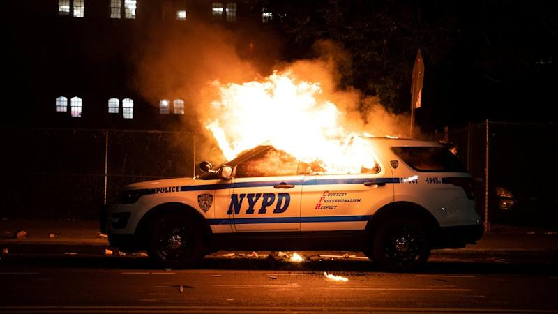 A NYPD police car is set on fire as protesters clash with police during a march against the death in Minneapolis police custody of George Floyd, in the Brooklyn borough of New York City, U.S., May 30, 2020