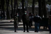 Migrants wearing protective face masks stand at the entrance of the Ritsona camp, after authorities found 20 coronavirus cases and placed the camp under quarantine, following the outbreak of coronavirus disease (COVID-19), in Ritsona