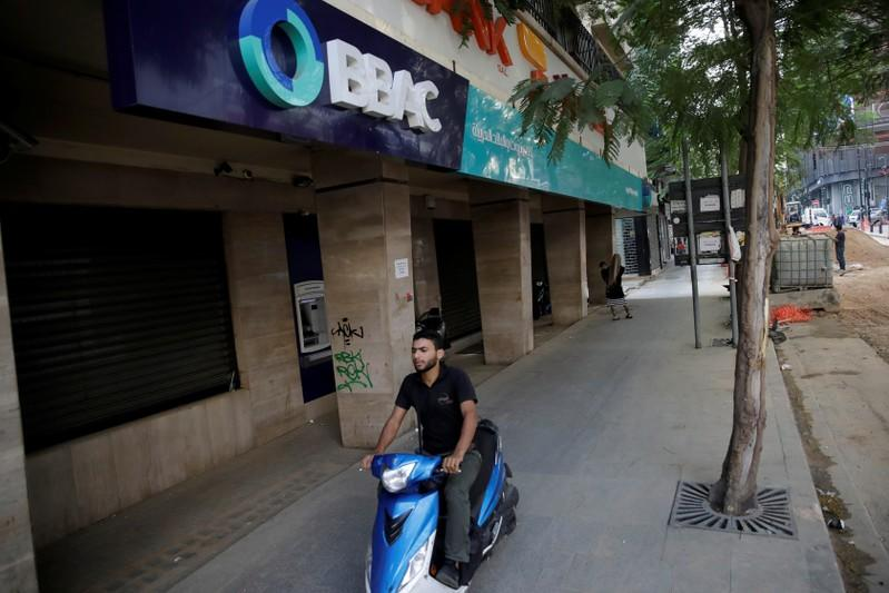 A man drives a motorbike past a closed bank office in Beirut