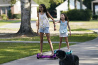 Cecilia Shaffette plays in the driveway with her sister Lydia, right, at their home in Carriere, Miss., Wednesday, June 16, 2021. (AP Photo/Gerald Herbert)