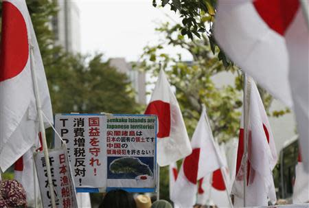 "A member of the nationalist movement ""Ganbare Nippon"" holding a placard of disputed islands known as Senkaku in Japan and Diaoyu in China, walks among Japanese national flags during a rally in Tokyo September 11, 2013, on the day of one year anniversary of Japanese government signed contract to buy islands disputed with China from a private owner. REUTERS/Toru Hanai"