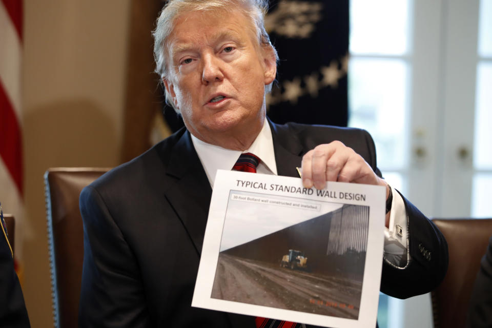 President Donald Trump holds a photo as he leads a roundtable discussion on border security with local leaders, Friday Jan. 11, 2019, in the Cabinet Room of the White House in Washington. (Photo credit: AP Photo/Jacquelyn Martin)