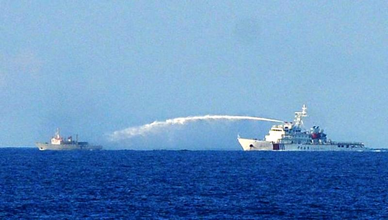 A Chinese Coastguard ship (R) uses a water cannon to attack a Vietnamese Fisheries Surveillance boat near the site of the Chinese oil rig in disputed waters of the South China Sea off Vietnam's central coast, June 2, 2014