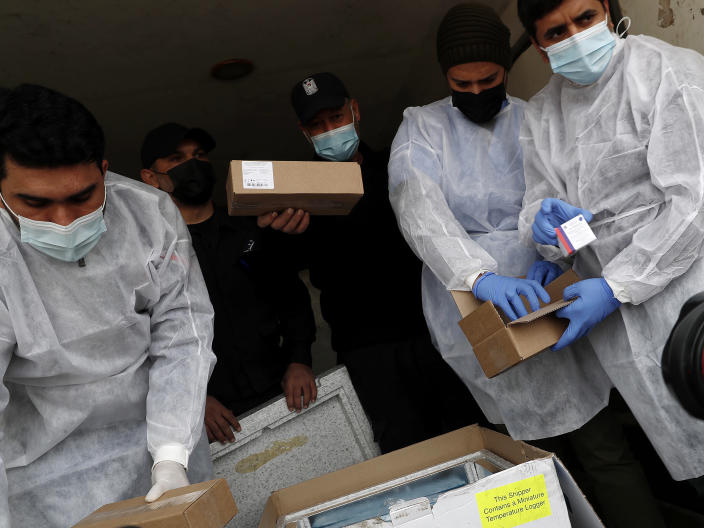 Medics and police officers check a shipment of the Russian Sputnik V vaccine inside a truck at the Kerem Shalom border crossing, in Rafah, Gaza Strip, Wednesday, Feb. 17, 2021. The Palestinian Authority said Wednesday that it dispatched the first shipment of coronavirus vaccines to the Hamas-ruled Gaza Strip, two days after accusing Israel of preventing it from sending the doses amid objections from some Israeli lawmakers. (AP Photo/Adel Hana)