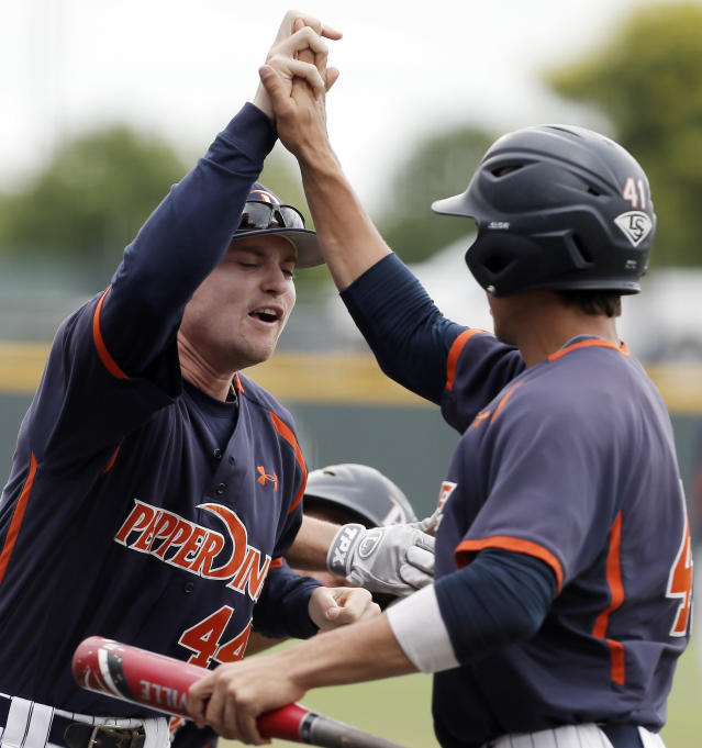 Pepperdine's Brandon Caruso (41) is congratulated by teammate Connor Garelick (44) after scoring a run on an RBI by teammate Aaron Brown, not pictured, during the first inning of an NCAA college baseball tournament super regional game against the TCU in Fort Worth, Texas, Monday, June 9, 2014. (AP Photo/Brandon Wade)