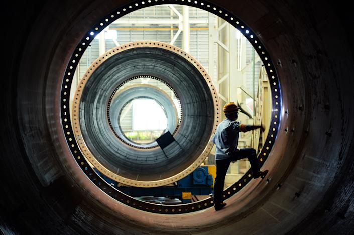 A wind turbine factory worker stands inside a large circular wind turbine component.