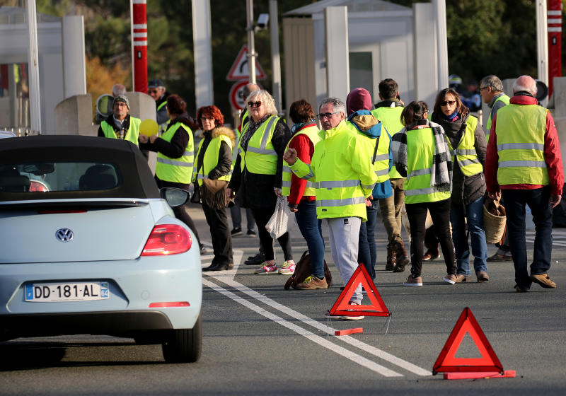 "Demonstrators wearing yellow vests protest at the toll gates of a motorway, in Biarritz, southwestern France, Monday, Dec. 10, 2018. French President Emmanuel Macron will be speaking to his nation at last Monday, after increasingly violent, radicalized protests against his leadership have shaken the country and scarred its beloved capital. His long silence has aggravated that anger and many protesters are hoping only to hear one thing from Macron: ""I quit."" (AP Photo/Bob Edme)"