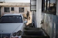 A soldier patrols as police search the hostels