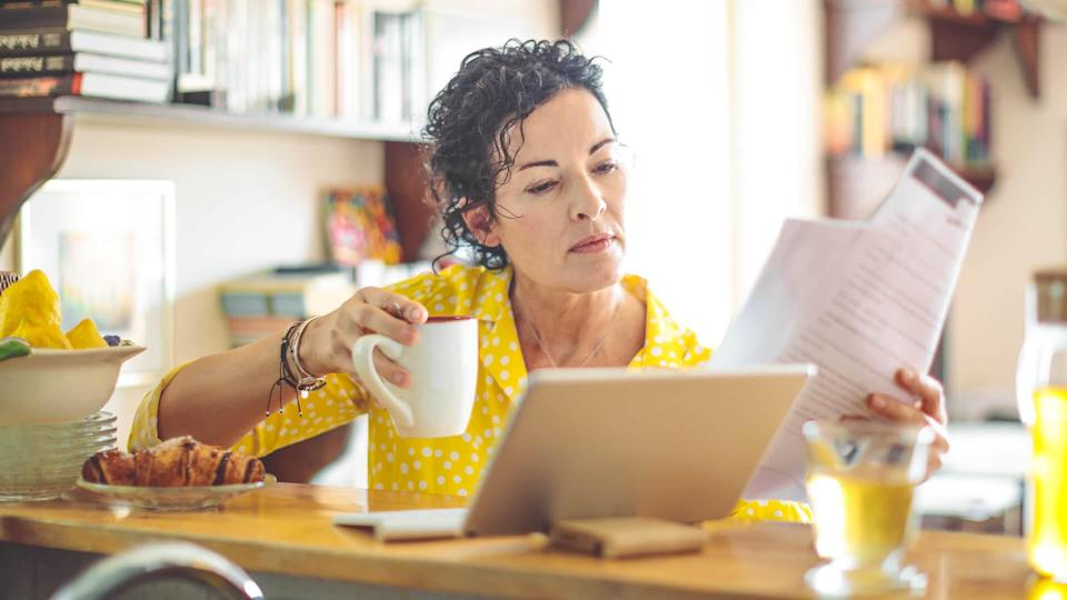 Mature woman is checking her finances at home.