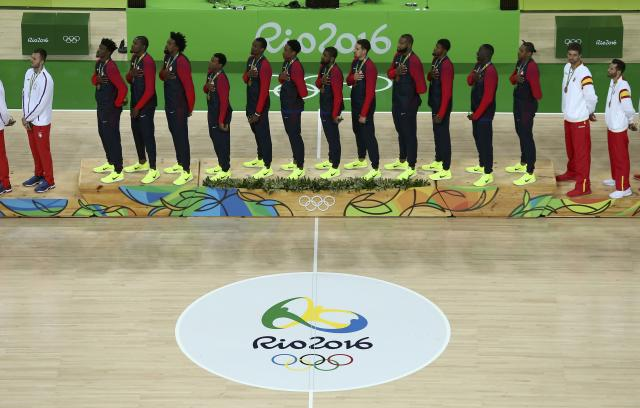 2016 Rio Olympics - Basketball - Final - Men's Gold Medal Game Serbia v USA - Carioca Arena 1 - Rio de Janeiro, Brazil - 21/8/2016. United States players stand with their gold medals for the playing of the U.S. National Anthem during the presentation ceremony for men's basketball. REUTERS/Antonio Bronic FOR EDITORIAL USE ONLY. NOT FOR SALE FOR MARKETING OR ADVERTISING CAMPAIGNS.