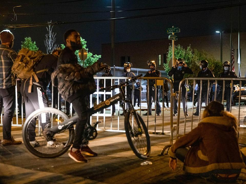 A group of protesters face police barricading the 18th Police Precinct after the city imposed a 9pm curfew in Philadelphia, (AFP via Getty Images)