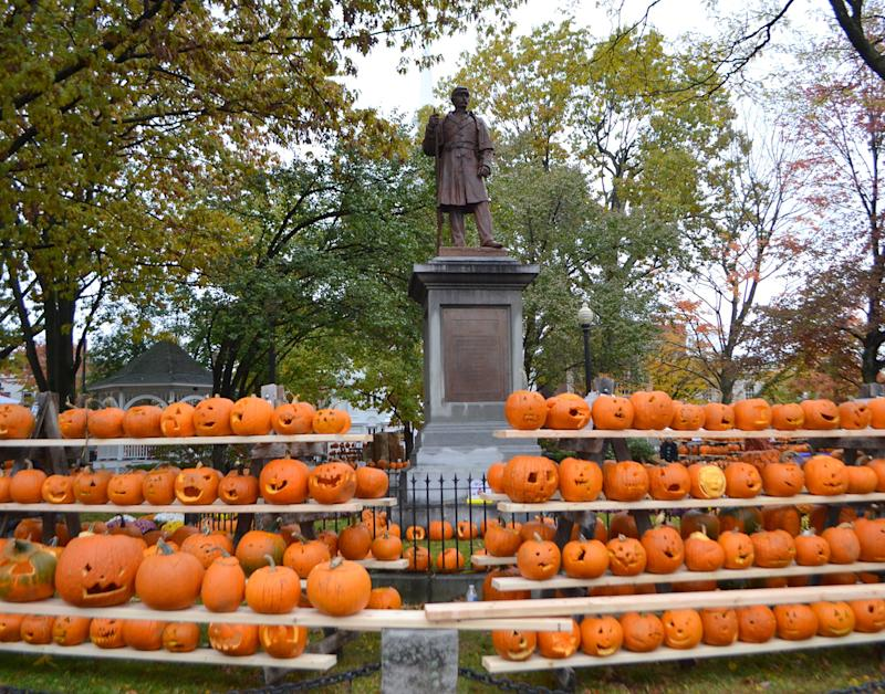 Rows of carved pumpkins on shelves in front of historical statue