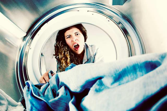 Horrified young woman grimaces at laundry in clothes drier