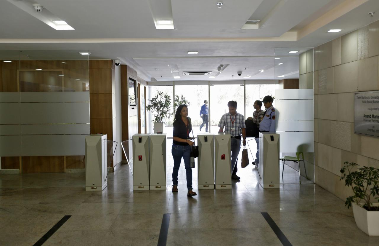 "Employees arrive for work at Tech Mahindra office building in Noida on the outskirts of New Delhi March 18, 2013. India's IT outsourcers are promoting ""mini CEOs"" capable of running businesses on their own, while trimming down on the hordes of entry-level computer coders they normally hire as they try to squeeze more profits out of their staff. To match Analysis INDIA-TECH/STAFFING  Picture taken March 18, 2013. REUTERS/Adnan Abidi (INDIA - Tags: BUSINESS SCIENCE TECHNOLOGY EMPLOYMENT)"