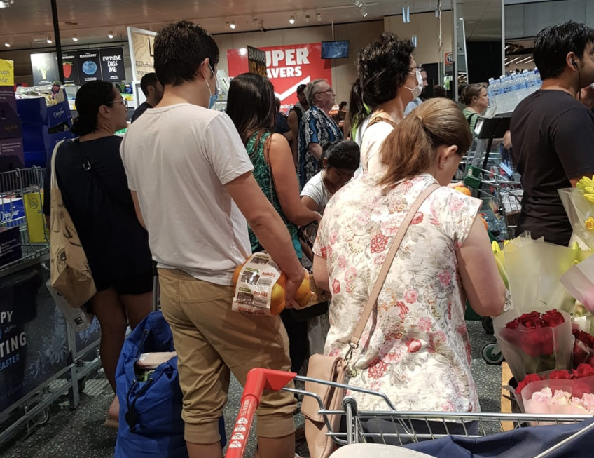 Customers are seen lining up next to each other in Aldi.
