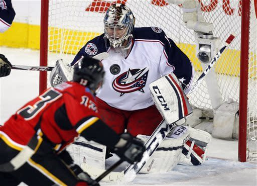 Columbus Blue Jackets goalie Steve Mason, right, stops a shot from Calgary Flames' Mike Cammalleri during the second period of an NHL hockey game Friday, March 29, 2013, in Calgary, Alberta. (AP Photo/The Canadian Press, Jeff McIntosh)
