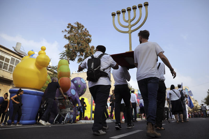 """FILE - In this Oct. 17, 2019 file photo, people carry a Menorah as they participate in the annual support march for Israel, during the Jewish holiday of Sukkot, in Jerusalem. An evangelical broadcaster who boasted of miraculously securing a TV license in Israel now risks being taken off the air over suspicions of trying to convert Jews to Christianity. The controversy over """"GOD TV"""" has put both Israel and its evangelical Christian allies in an awkward position. Evangelical Christians, particularly in the United States, are among Israel's strongest supporters. Israel has long welcomed their political and financial support, especially as their influence has risen during the Trump era. (AP Photo/Oded Balilty, File )"""