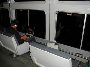 Man using laptop on a train