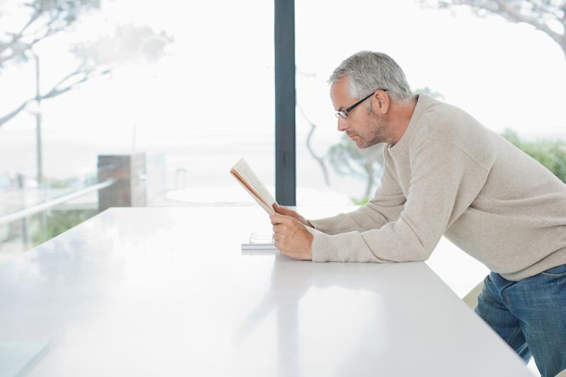 Older man leaning on table while reading newspaper