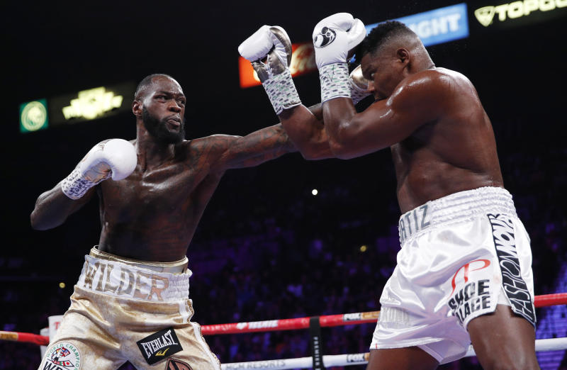 Deontay Wilder, left, fights Luis Ortiz in a heavyweight title boxing match Saturday, Nov. 23, 2019, in Las Vegas. (AP Photo/John Locher)