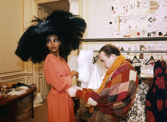 <p>French fashion designer Christian Lacroix works on his 1987 spring-summer haute couture line for Patou. Fashion model Kadija is wearing a large black hat with a rose-colored dress.</p>