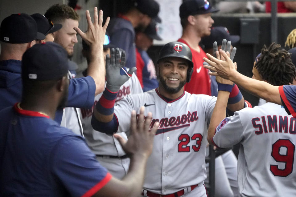 Minnesota Twins' Nelson Cruz celebrates in the dugout his home run off Chicago White Sox's Lance Lynn during the sixth inning of a baseball game Monday, July 19, 2021, in Chicago. (AP Photo/Charles Rex Arbogast)