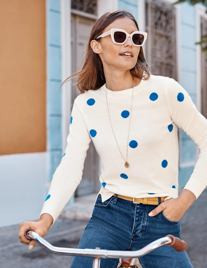 Woman on a bike wearing a Boden spotty cashmere jumper