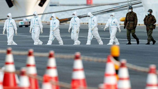 PHOTO: Workers and army officers wearing protective suits walk away from the Diamond Princess cruise ship, as they prepare to transfer passengers tested positive for the novel coronavirus, in the Japanese port of Yokohama, Feb. 10, 2020. (Kim Kyung Hoon/Reuters)