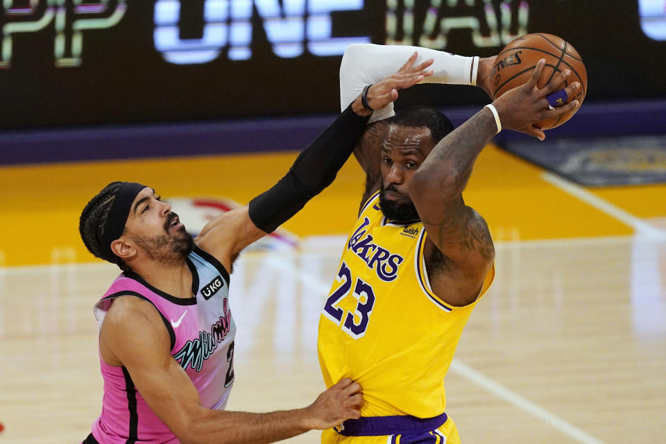 Los Angeles Lakers forward LeBron James, right, tries to pass as Miami Heat guard Gabe Vincent defends during the first half of an NBA basketball game Saturday, Feb. 20, 2021, in Los Angeles. (AP Photo/Mark J. Terrill)