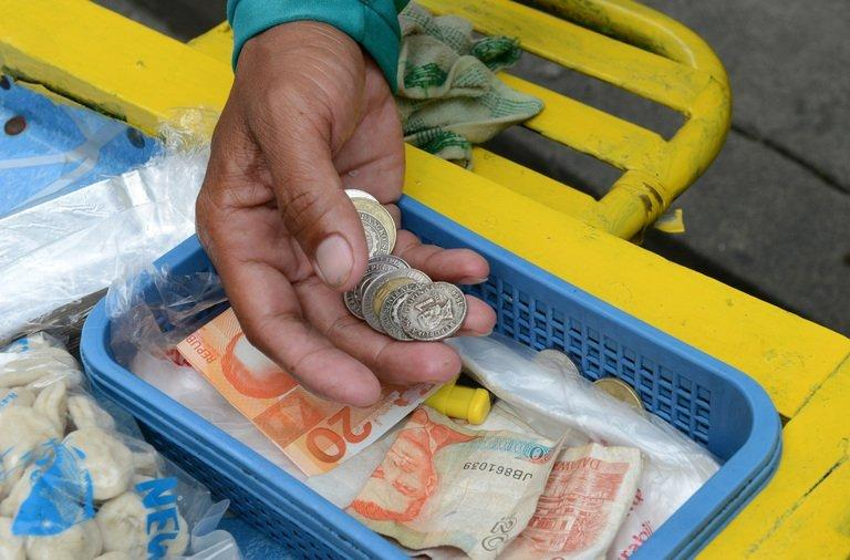 A street vendor counts Philippine pesos in Manila on September 13, 2012
