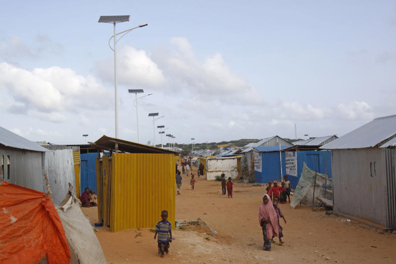In this photo of Wednesday, July 17, 2013, Somali's walk past solar powered lights at a refugee camp in Mogadishu, Somalia. The sound of chatting women sitting outside makeshift homes while children play games nearby is a new scene in a once pitch-dark refugee camp in the Somali capital, reclaiming ground that had been ruled by stray cats and roaming rapists. For months, women avoided leaving home or using the communal bathrooms at night because men armed with knives and guns frequently entered the camps and ambushed them as they went to the bathrooms and then dragged them into nearby dark shrubs to rape them. (AP Photo/Farah Abdi Warsameh)