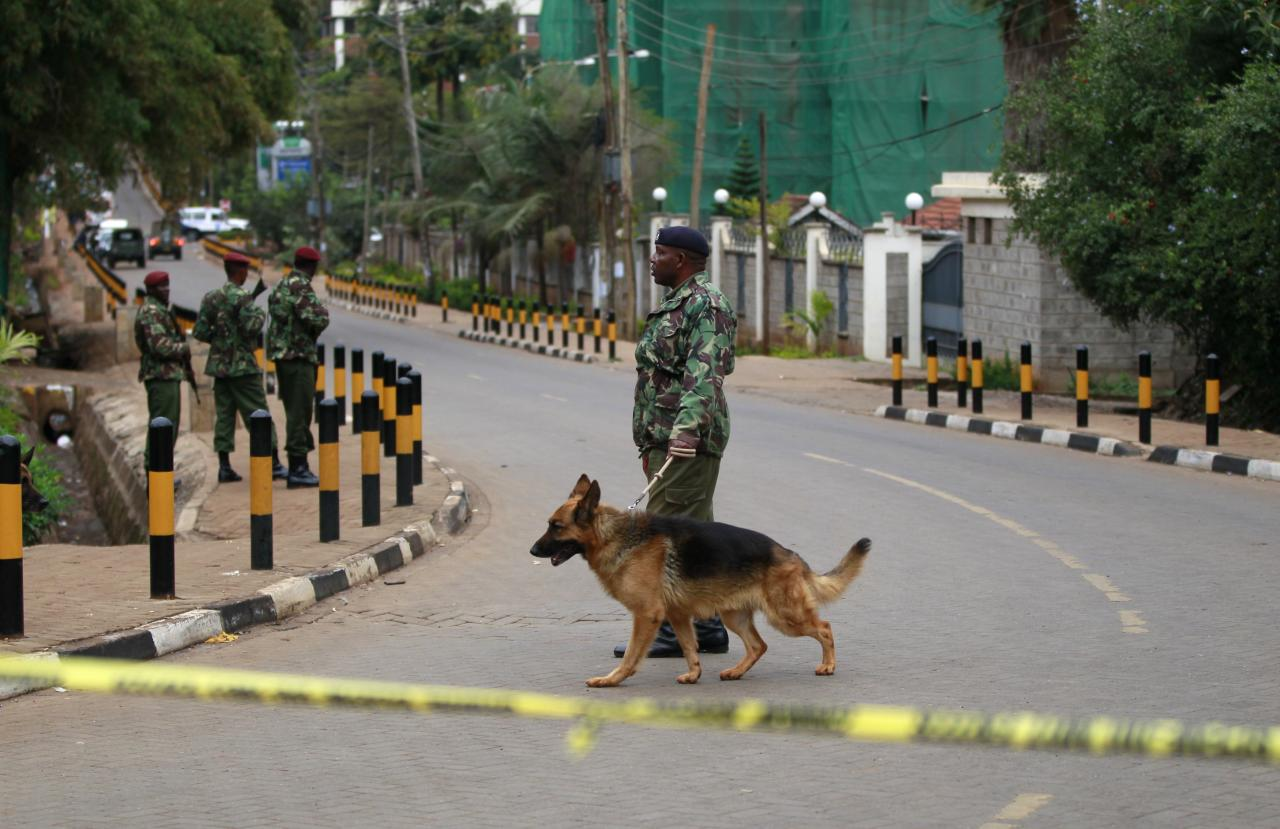 A policeman patrols with his dog near the Westgate Shopping Centre in Kenya's capital Nairobi September 22, 2013. Kenyan security forces were locked in a stand-off on Sunday with gunmen who killed at least 39 people at an upmarket shopping mall in the Kenyan capital, and it was still unclear how many hostages the al Qaeda-linked militants were holding. REUTERS/Thomas Mukoya (KENYA - Tags: SOCIETY CIVIL UNREST CRIME LAW ANIMALS)