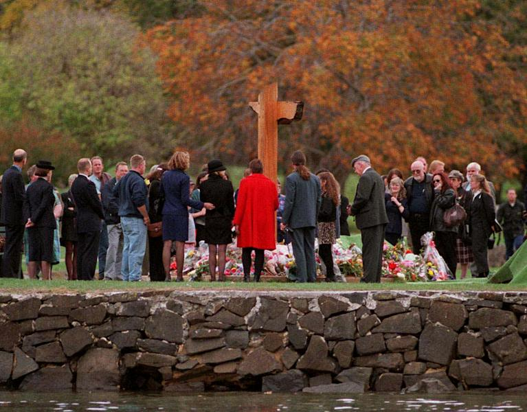 FILE - In this April 28, 1997 file photo, families and friends gather around the memorial at the old convict settlement for a minute's silence at a service in memory of the 35 people killed, on the first anniversary of a rampage there by lone gunman Martin Bryant, in Port Arthur, Tasmania. Supporters of gun control often cite Australia's dramatic response to a 1996 shooting spree in the southern state of Tasmania that killed 35 people. The slaughter sparked outrage across the country and within 12 days federal and state governments had agreed to impose strict new gun laws, including a ban on semi-automatic rifles like the Colt AR-15 used by the Tasmania killer. (AP Photo/Leigh Winburn, Pool-File)