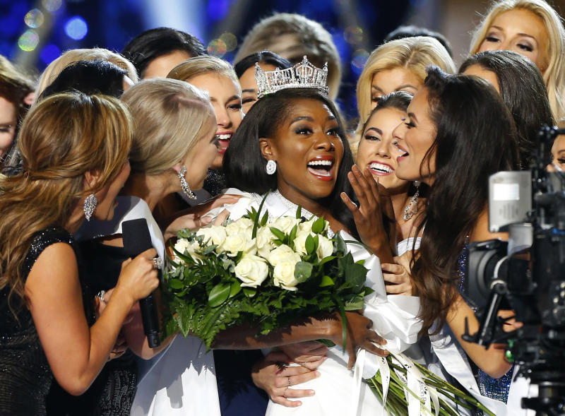 FILE - This Sept. 9, 2018 file photo shows Miss New York Nia Franklin, center, reacting after being named Miss America 2019 in Atlantic City, N.J. The Miss America Organization says this year's pageant will be held at the Mohegan Sun Connecticut in Uncasville, Connecticut. It will be broadcast on NBC Dec. 19, in a switch from recent broadcaster ABC. (AP Photo/Noah K. Murray, File)