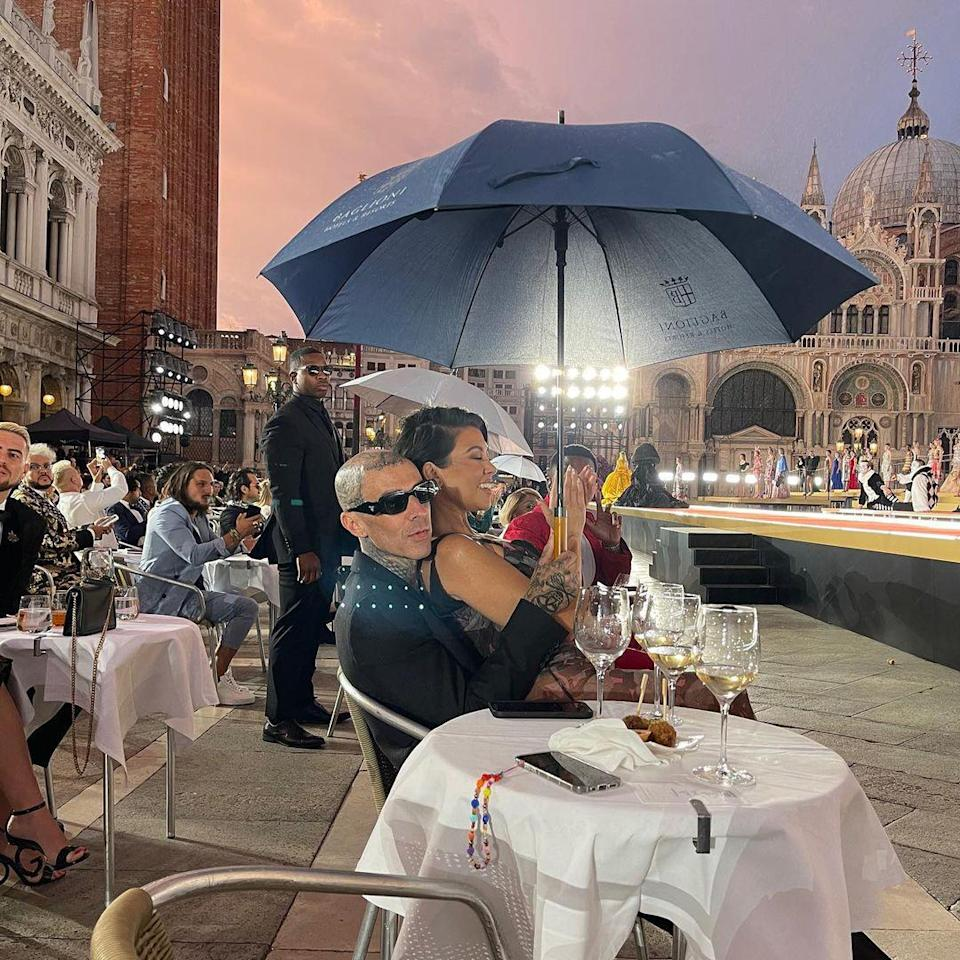 <p>There's no raining on their parade! The couple cozied up under an umbrella while sitting front row at the show. </p>