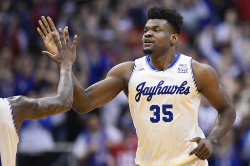 FILE - In this Feb. 3, 2020, file photo, Kansas center Udoka Azubuike (35) is congratulated after a dunk against Texas during the second half of an NCAA college basketball game in Lawrence, Kan. Azubuike was selected by the Utah Jazz in the NBA draft Wednesday, Nov. 18, 2020. (AP Photo/Reed Hoffmann, File)