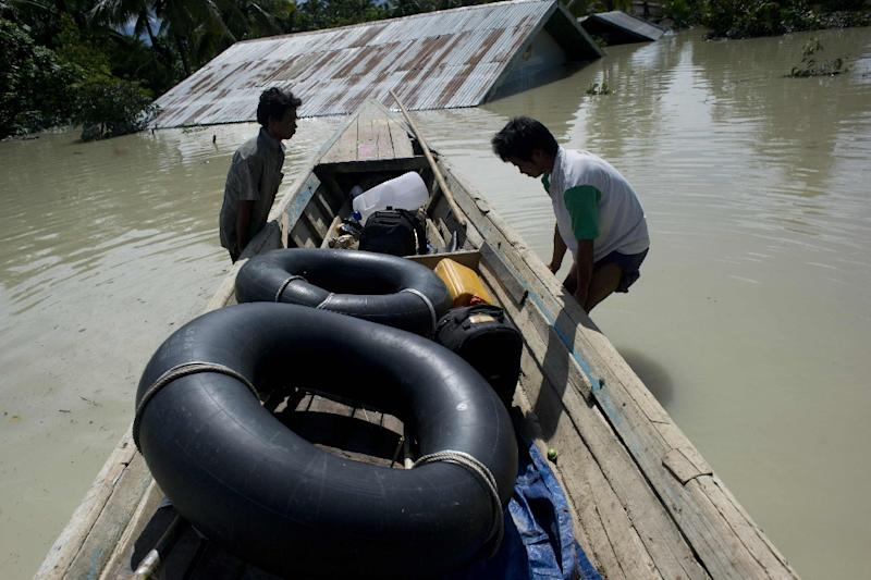Residents transport rubber tubes on a raft over floodwaters in Kalay, upper Myanmar's Sagaing region, on August 2, 2015 (AFP Photo/Ye Aung Thu)