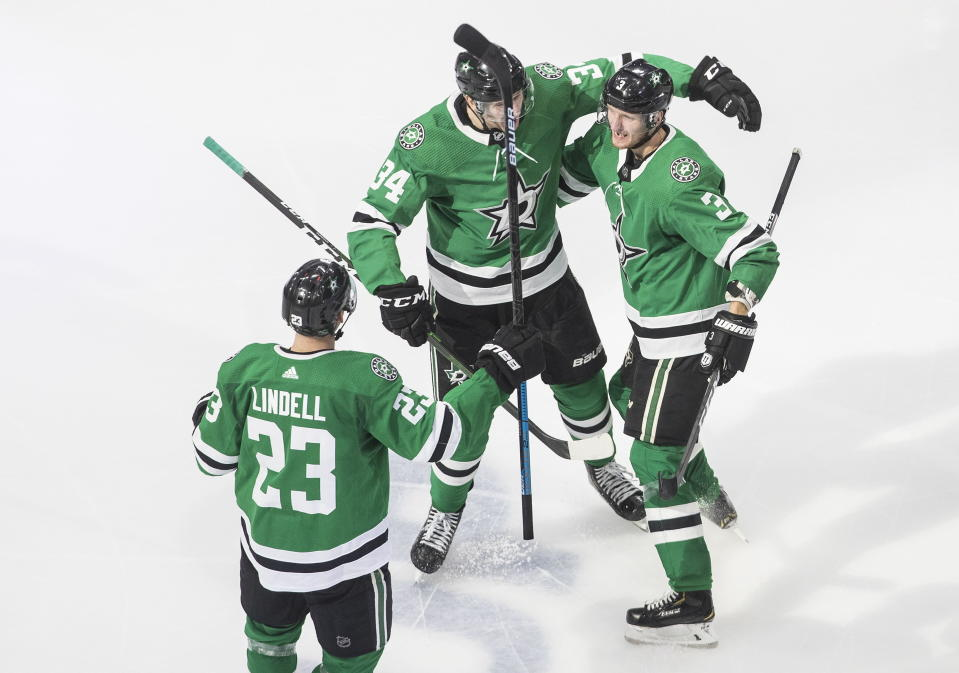 Dallas Stars' Esa Lindell (23), Denis Gurianov (34) and John Klingberg (3) celebrate a goal during third period NHL Western Conference Stanley Cup playoff hockey action against the Calgary Flames in Edmonton, Alberta, Tuesday, Aug. 18, 2020. (Jason Franson/The Canadian Press via AP)