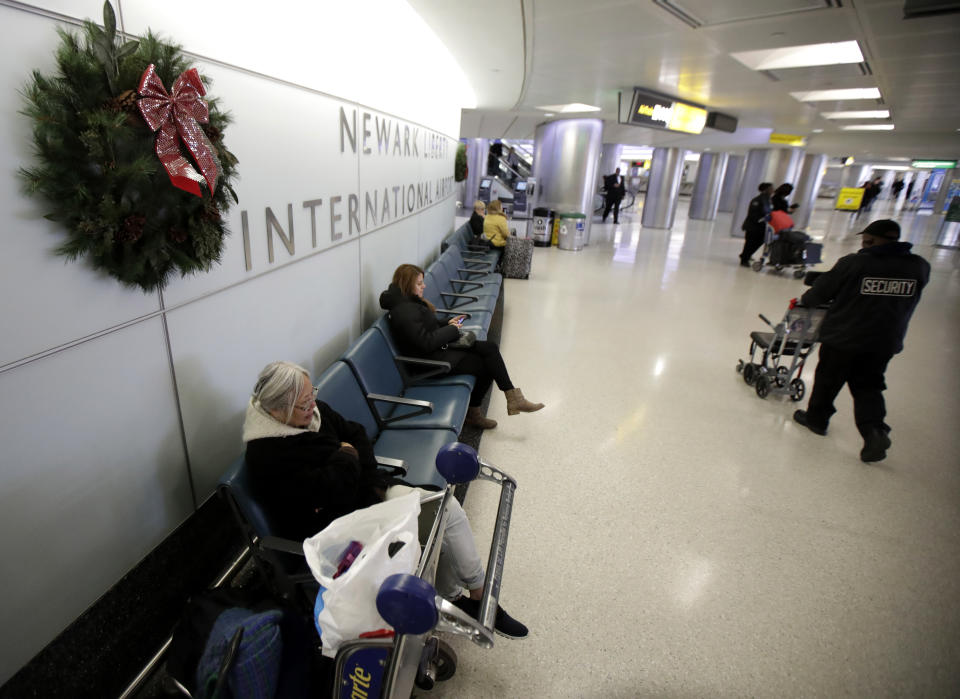 People wait near the baggage claim area at Terminal B at Newark Liberty International Airport, Tuesday, Nov. 21, 2017, in Newark, N.J. Early holiday travel has picked up at the airport with travelers flying on Tuesday ahead of the Thanksgiving Day holiday. (AP Photo/Julio Cortez)