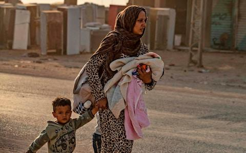 <span>A woman flees with her children in Ras al-Ain as Turkey begins its attack</span> <span>Credit: DELIL SOULEIMAN/ AFP </span>