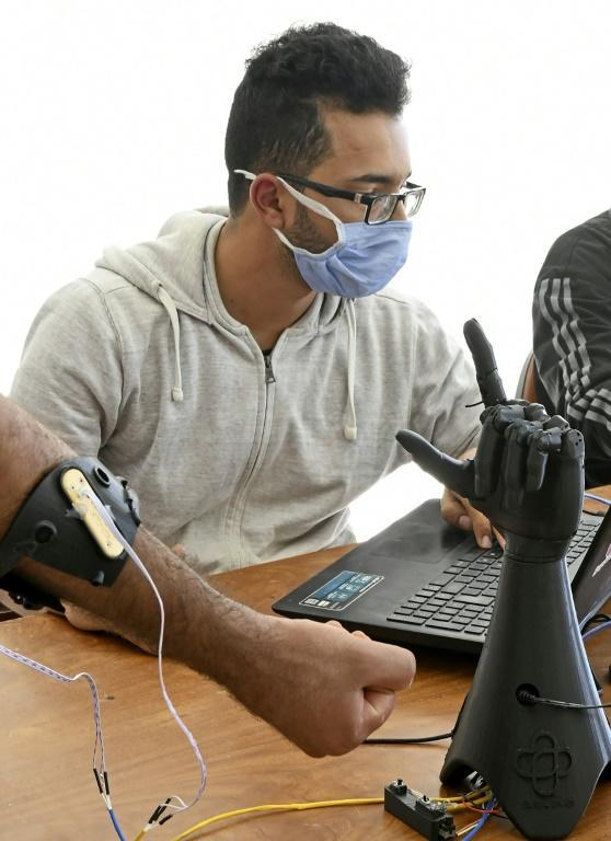 Tunisian engineers test a prototype of an artificial hand at the Cure Bionics startup in Sousse