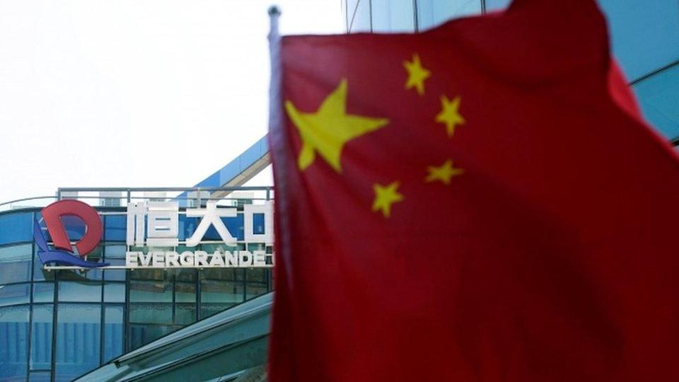Chinese flag with Evergrande Center, Shanghai in background.