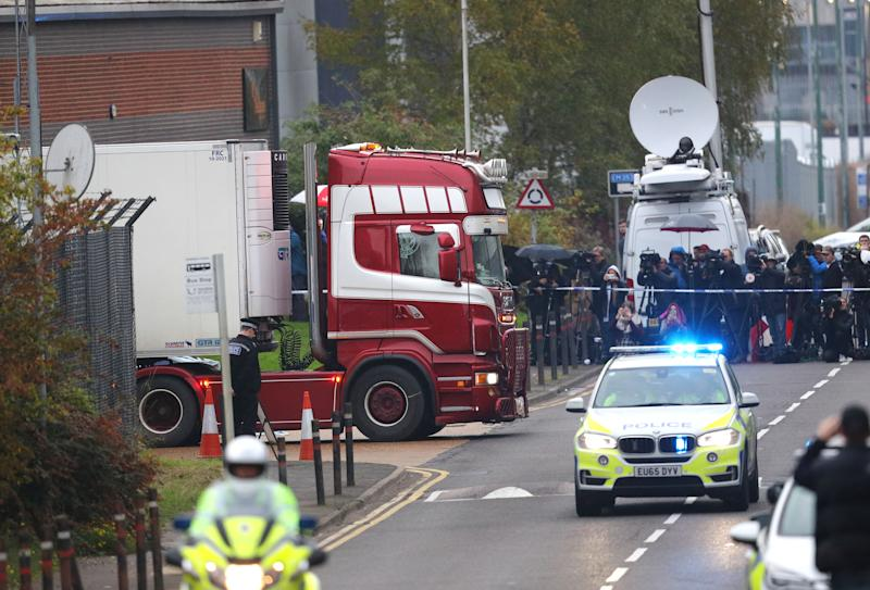 Media stand behind a police cordon as the lorry is moved from the Grays industrial estate shortly before 5pm on Wednesday. (PA)