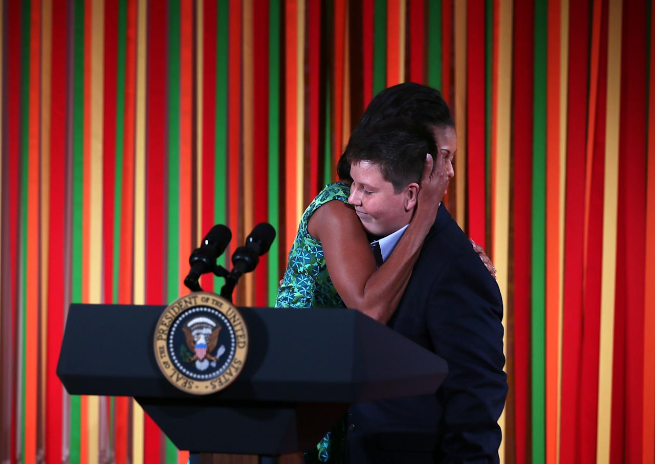 "WASHINGTON, DC - AUGUST 20:  U.S. first lady Michelle Obama hugs Marshall Reid, a judge of the Healthy Lunchtime Challenge, during a Kids' ""State Dinner"" luncheon at the East Room of the White House August 20, 2012 in Washington, DC. Fifty-four kids representing all U.S. states, three territories and the District of Columbia, ages 8-12 and winners of the Healthy Lunchtime Challenge to create a healthy, affordable and tasty lunchtime recipe with nutritional guidelines set by the Agriculture Department, were invited to participate in the event.  (Photo by Alex Wong/Getty Images)"