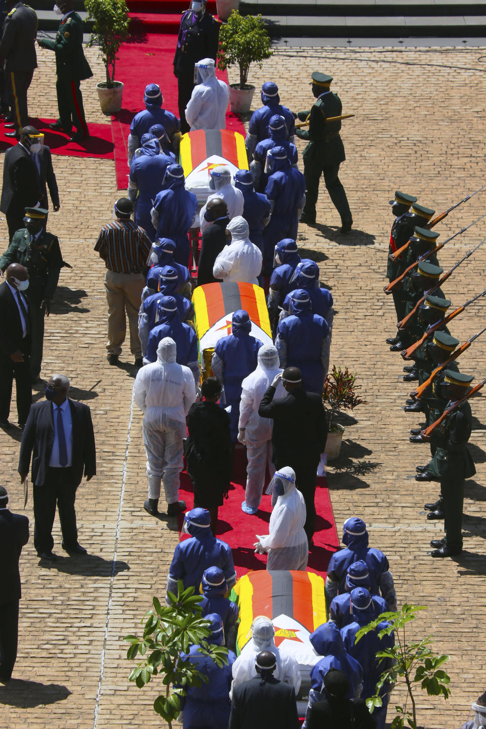 Pallbearers stand by the coffins of three top government officials prior to their burial, at the National Heroes Acre in Harare, Wednesday, Jan. 27, 2021. Zimbabwe on Wednesday buried three top officials who succumbed to COVID-19, in a single ceremony at a shrine reserved almost exclusively for the ruling elite as a virulent second wave of the coronavirus takes a devastating toll on the country. (AP Photo/Tsvangirayi Mukwazhi)