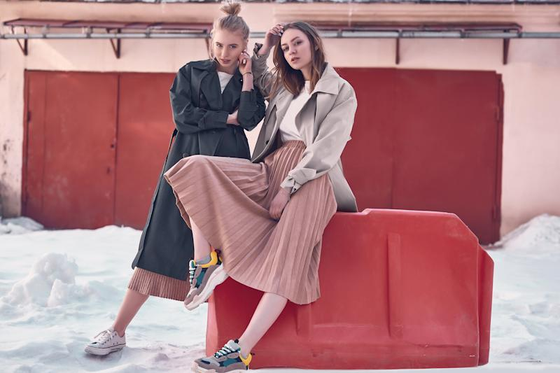 Two young women wearing sneakers and long skirts.