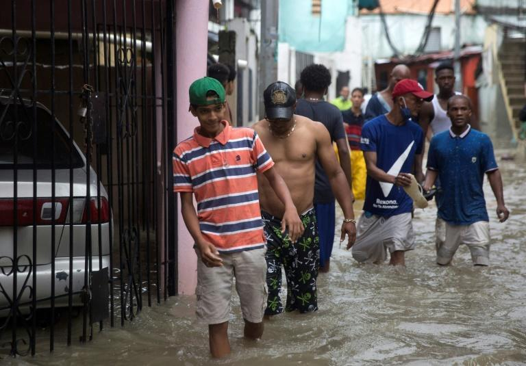 Men wade through a flooded street in Santo Domingo after Tropical Storm Laura caused destruction in the Dominican capital