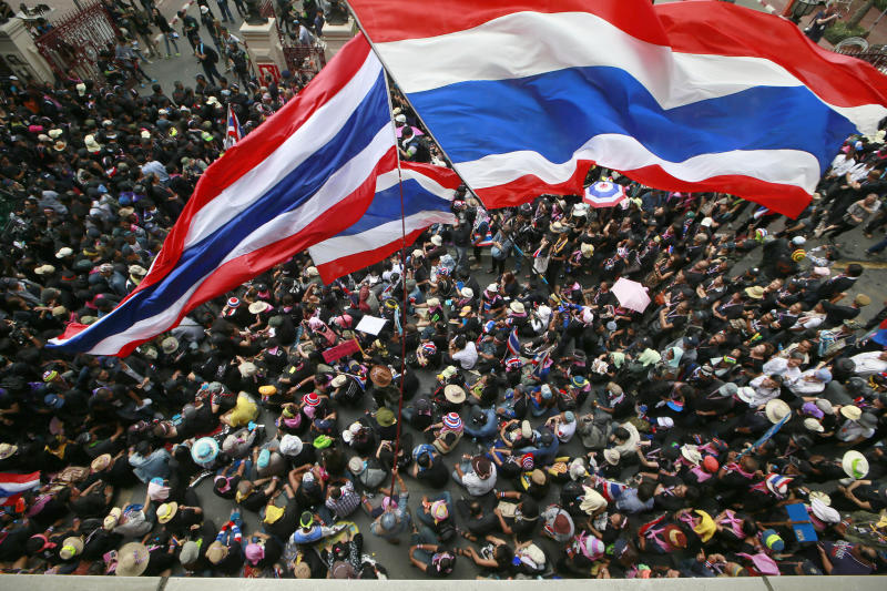Anti-government protesters wave national flags at the gates of the police headquarters during a memorial for the children killed in recent bomb blasts in Bangkok, Thailand, Wednesday, Feb. 26, 2014. Violence spread Tuesday to another anti-government protest site in Thailand's capital following weekend explosions that left five people dead, including four children, security officials said. (AP Photo/Wason Wanichakorn)