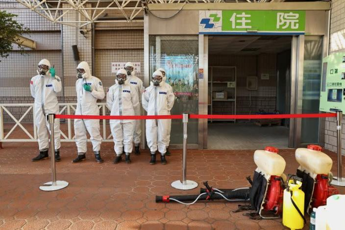Soldiers prepare to spray disinfectant outside the Taoyuan General Hospital in Taoyuan