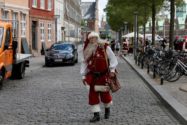 <p>A man dressed as Santa Claus walks through the streets between events for the World Santa Claus Congress, an annual event held every summer in Copenhagen, Denmark, July 23, 2018. (Photo: Andrew Kelly/Reuters) </p>